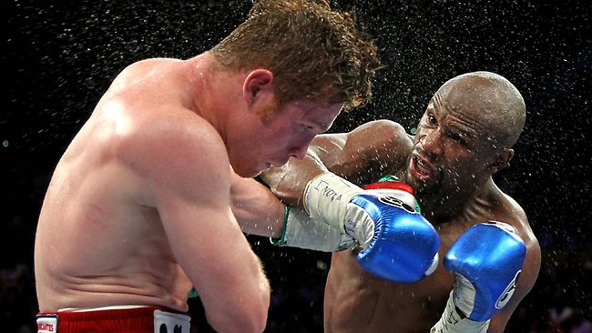 Boxers Floyd Mayweather Jr. of US (R) throws a left at Canelo Alvarez, Mexico, (L) during their WBC/WBA 154-pound title fight the MGM Grand Garden Arena.