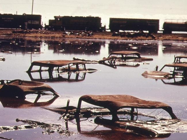 A train on the Southern Pacific Railroad passes a five-acre pond, which was used as a dump site by area commercial firms, near Ogden, Utah, in April of 1974. Picture: Documerica/US National Archives