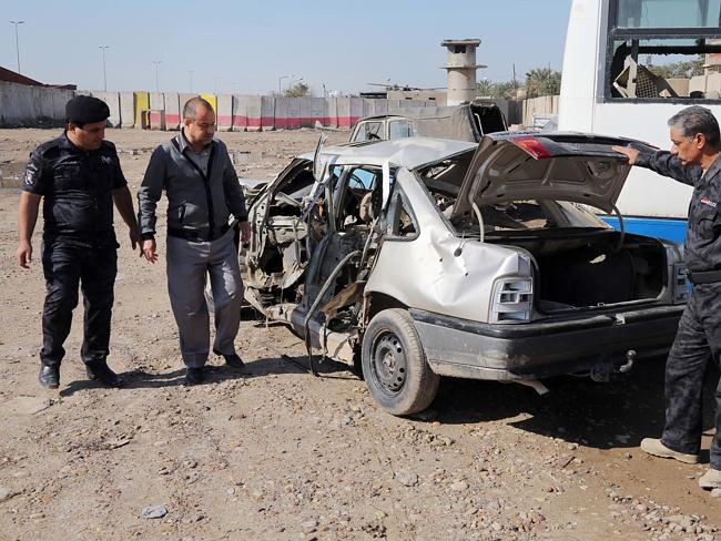 Deadly weapon ... Iraqi security forces inspect a car destroyed after a car-bomb attack in the Jamila neighbourhood of Baghdad, Iraq. Picture: AP /Karim Kadim