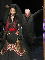 French designer Jean-Paul Gaultier, background, appears behind Austrian singer and Eurovision Song Contest winner Conchita Wurst , at the end of the Jean-Paul Gaultier Fall Winter 2014-15 Haute Couture collection, presented in Paris. Picture: AP