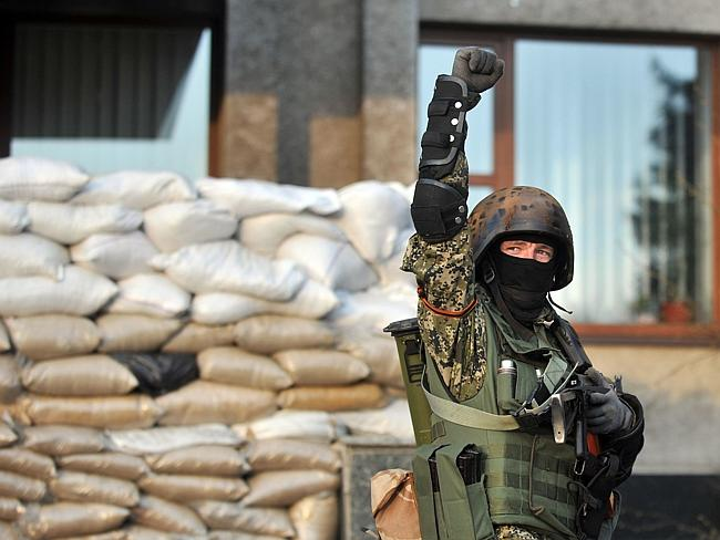 Peace deal ... An armed pro-Russian activist stands guard at a barricade outside the regi