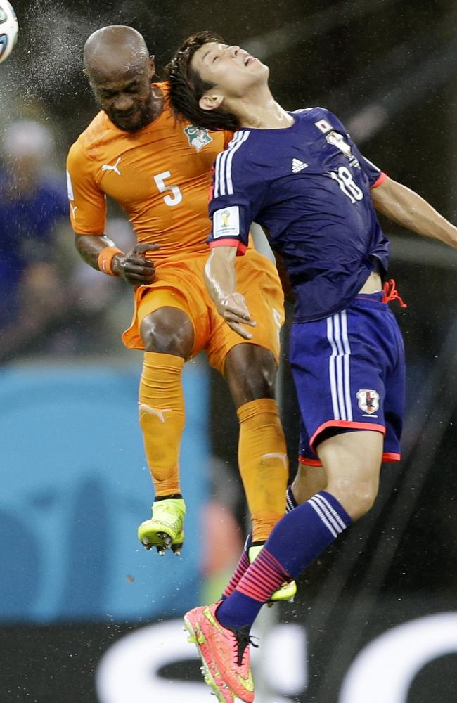Ivory Coast's Didier Zokora, left, challenges for the ball with Japan's Yuya Osako during their Group C World Cup match.