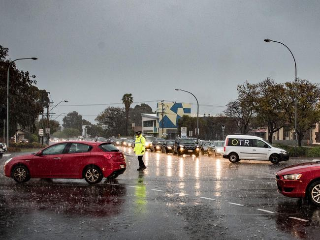 A lone policeman directs traffic in Adelaide after traffic lights went out amid lashing rain and hail. Picture by Matt Turner.