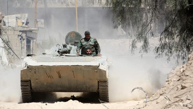 Syrian Army soldiers advancing in an area on the eastern outskirts of Douma, as they continue their fierce offensive. Picture: AFP