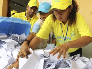 Electoral workers empty a ballot box as votes are counted during the parliamentary election in Dili, East Timor, Saturday, July 22, 2017. Almost two dozen parties are contesting in the polls that are likely to return independence heroes to power, despite frustration in the young democracy with lack of economic progress and warnings the country could be bankrupt within a decade. (AP Photo/Kandhi Barnez)
