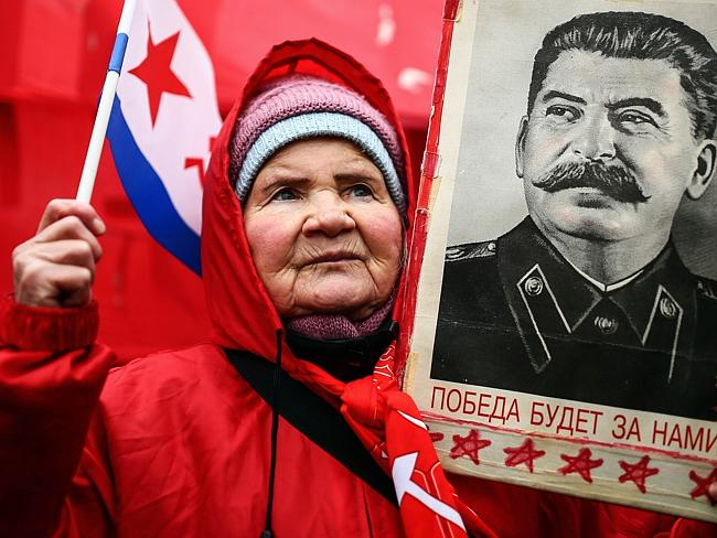 """Old guard ... a Russian Communist holds up a portrait of former Soviet dictator Josef Stalin during a rally marking """"Defender of the Fatherland Day"""" in Moscow on February 23. Picture: Mikhail Listopadov"""