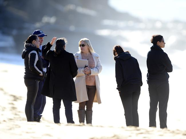Police speak with distraught people, during the search. Picture: Peter Clark