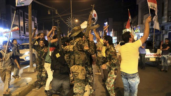 Iraqi security and civilians celebrate while holding national flags as they wait for the final announcement of the defeat of the Islamic state militants, in Basra, 550 kilometres southeast of Baghdad. Picture: AP