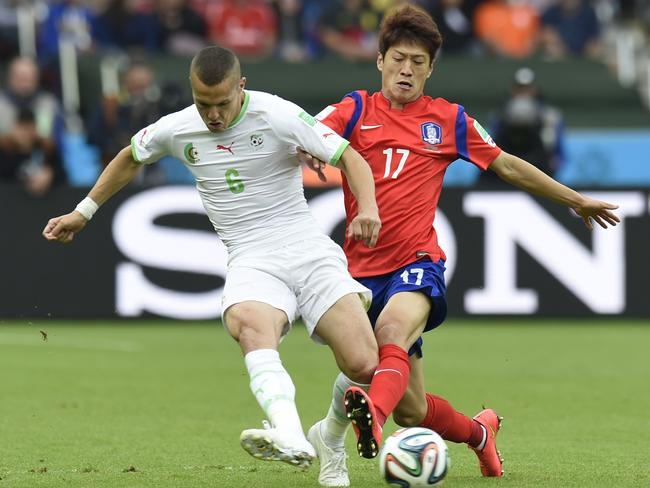 South Korea's midfielder Lee Chung-Yong challenges Algeria's defender Djamel Mesbah.