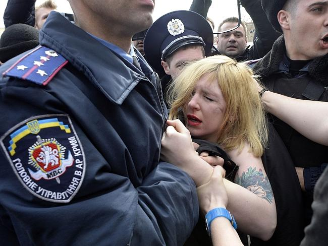 Arrested ... Ukrainian police officers detain a topless activist of the Ukrainian women m