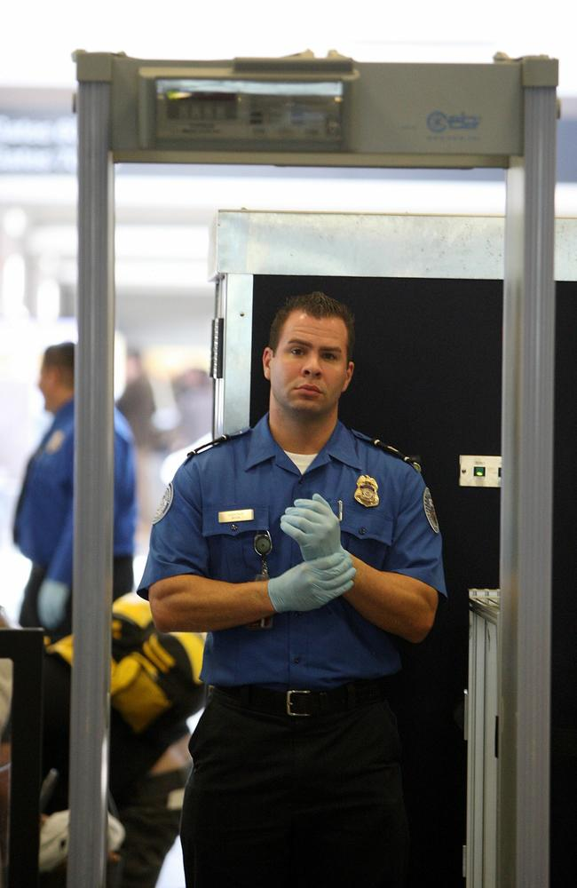 A TSA agent waits for passengers to pass through a magnetometer at LAX.