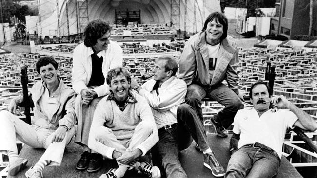 British comedy troupe Monty Python including (left to right) Michael Palin, Terry Jones, Eric Idle, Graham Chapman (1941 - 1989), Terry Gilliam, and John Cleese, lounge about at the site of their filmed live show at the Hollywood Bowl, Hollywood, California, 1982. Chapman and Cleese smoke pipes.