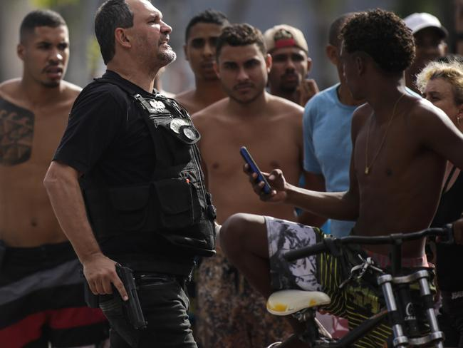 "A Civil Police officer yells ""get back"" to a crowd calling him out for shooting a minor in the leg who was attempting to loot an electronic store, in Vitoria, Espirito Santo state, Brazil. Picture: Diego Herculano/AP"