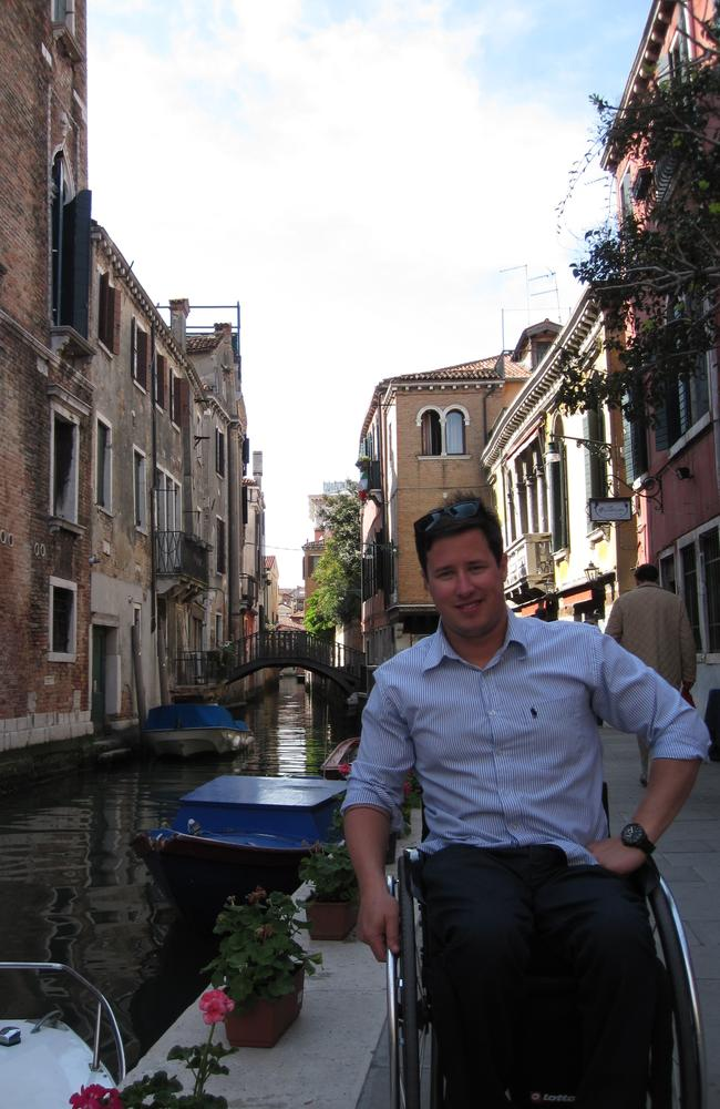 Scott Crowley, in his wheelchair next to a canal in Venice Italy, there are buildings behind him and boats on the canal