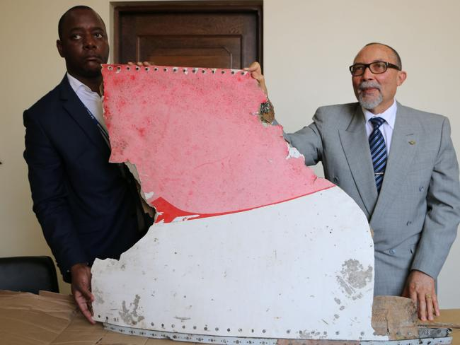 Joao de Abreu, right, President of Mozambique's Civil Aviation Institute (IACM), and a marshal display the suspected wreckage. Picture: Adrien Barbier/AFP