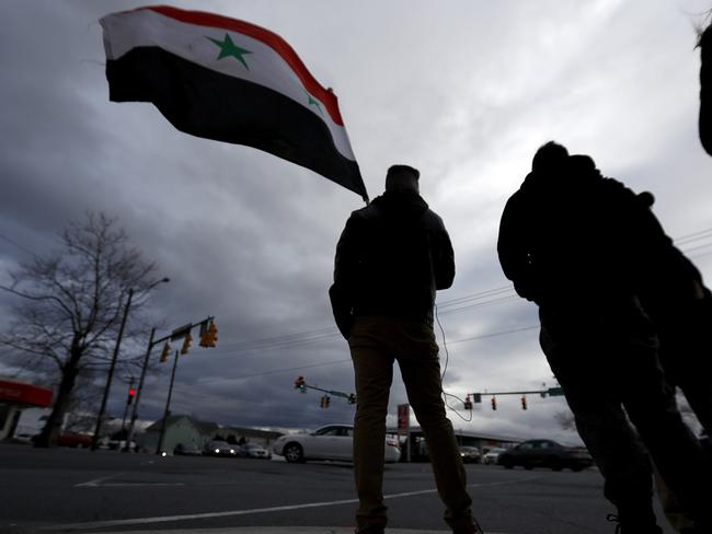 A man holds a Syrian flag during a rally in opposition to the US missile strikes in Syria in Allentown, Pennsylvania. Allentown has one of the nation's largest Syrian populations. They are mostly Christian and support Syrian President Bashar al-Assad. Picture: Julio Cortez/AP