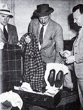Police detectives show the dead man's suitcase and belongings.