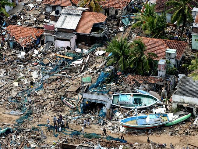 An aerial view of Sri Lankan survivors standing in the wreckage of houses, fishing boats and holiday resorts lashed by tsunamic waves at Kalmunai on 29 December 2004. Picture: AFP / Sena Vidanagama