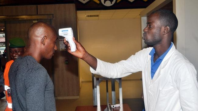A health agent checks a passenger leaving Guinea / Picture: AFP