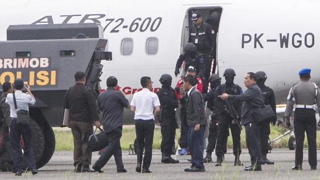 Arrival ... officers escort Andrew Chan from the plane at Cilacap in Central Java.