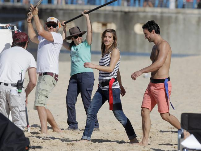 Brooke Satchwell and Glen McMillan from the cast of  <i>Wonderland</i> are filmed playing Oztag at Sydney's Coogee Beach. Picture: Nicolas Gonzalez