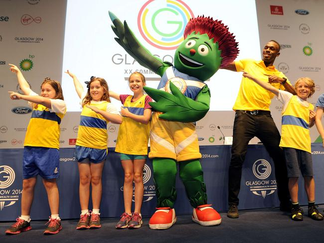 Bolt poses with local children and the Commonwealth Games mascot.