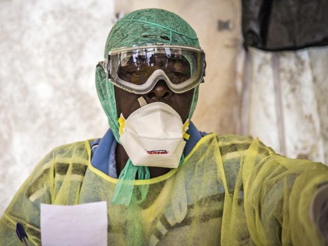 A health worker ... examines patients for Ebola inside a screening tent, at the Kenema Government Hospital situated in the Eastern Province around 300km from the capital city of Freetown in Kenema, Sierra Leone. Picture: AP/ Michael Duff