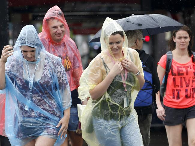 Tourists Maree Olerenshaw, Martino Sorace and Kylie King from Tasmania, Sydney and Brisbane put on ponchos to keep out the rain while they are on holiday in Cairns. Picture: Anna Rogers