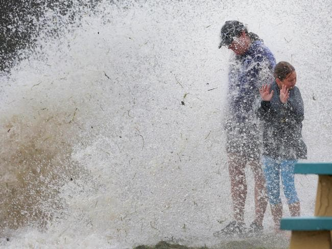 Wayne Ritchie and his daughter Dakota are hit by a wave crashing over the wall along the Wynnum Esplanade. Picture: Darren England