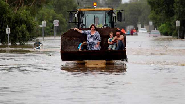Families that have been swept away in the cars or from flooded homes are being rescued by whatever means necessary. Picutre: The Courier Mail