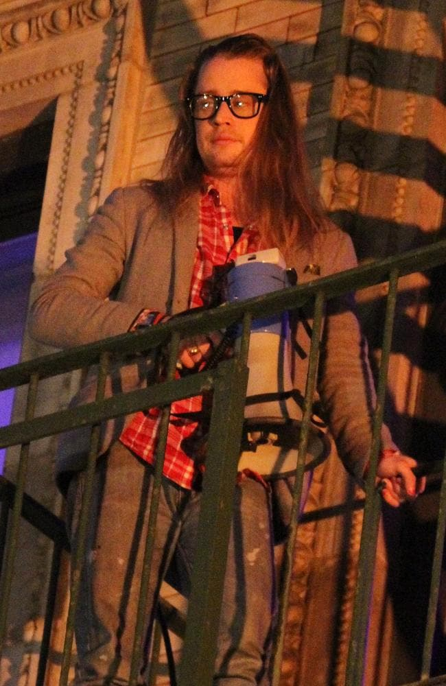 Macaulay Culkin pictured standing outside on the fire escape stairs as he films scenes for 'The Jim Gaffigan Show' in Soho, New York. Picture: Splash News Australia