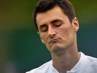 (FILES) A file photo taken on July 4, 2017, shows Australia's Bernard Tomic reacting against Germany's Mischa Zverev during their men's singles first round match on the second day at 2017 Wimbledon Championships in London. Apathetic Australian star Bernard Tomic has admitted he is playing tennis just for the money and says he has no love for the game that has earned him millions. In a frank Australian television interview on July 23 July, Tomic told his fans to stay at home rather than paying to watch him play if they were opposed to his polarising on-court antics. / AFP PHOTO / JUSTIN TALLIS / -- IMAGE RESTRICTED TO EDITORIAL USE - STRICTLY NO COMMERCIAL USE --