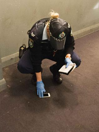 A police officer finds an iPhone behind a door in a corridor in the Astoria Hotel. Picture: Chris McKeen