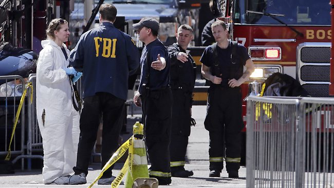 Boston firefighters, right, talk with FBI agents and a crime scene photographer at the scene of Monday's Boston Marathon explosions, which killed at least three and injured more than 140, in Boston, Tuesday, April 16, 2013. (AP Photo/Charles Krupa)
