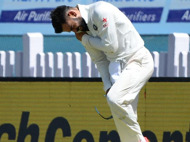Virat Kohli (R) holds his shoulder after he was injured while fielding during the first day of the third Test cricket match between India and Australia.