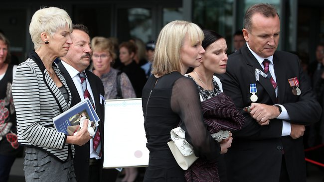 Damian's wife Sonya (front) is comforted by friends and family. Picture: Adam Head