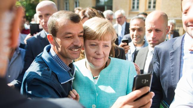 A migrant taking selfie picture with Angela Merkel following Merkel's visit at a branch of the Federal Office for Migration and Refugees and a camp for asylum-seekers in Berlin. (Photo: Bernd von Jutrczencka/AFP/DPA)