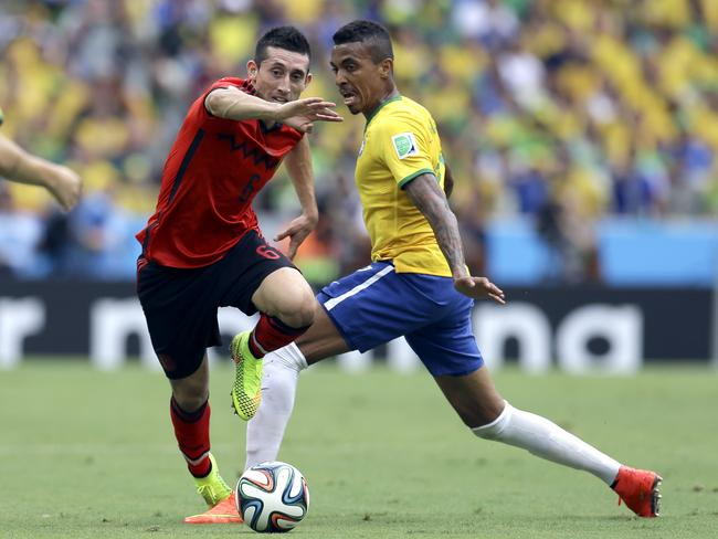 Mexico's Hector Herrera, left, gets past Brazil's Luiz Gustavo.