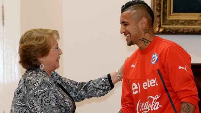 Chile's President Michelle Bachelet (L) shakes hands with Arturo Vidal.