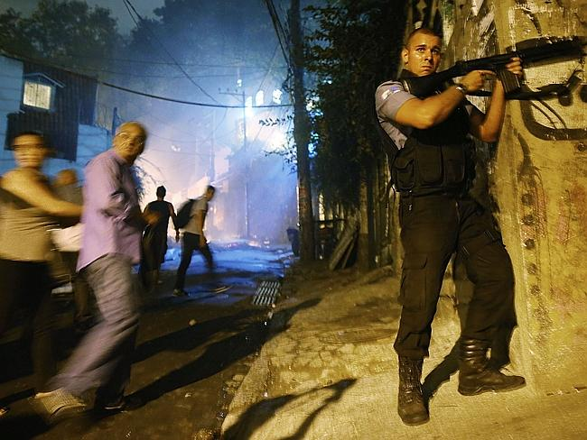 People flee ... Brazilian military police officer aims his weapon following shootings in the 'pacified' Pavao-Pavaozinho community. Picture: Mario Tama