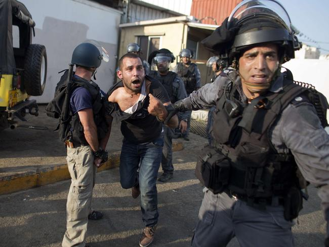 Getting loud ... Israeli riot police arrest an Arab Israeli man during clashes that followed a protest against Israel's military offensive on the Gaza Strip.