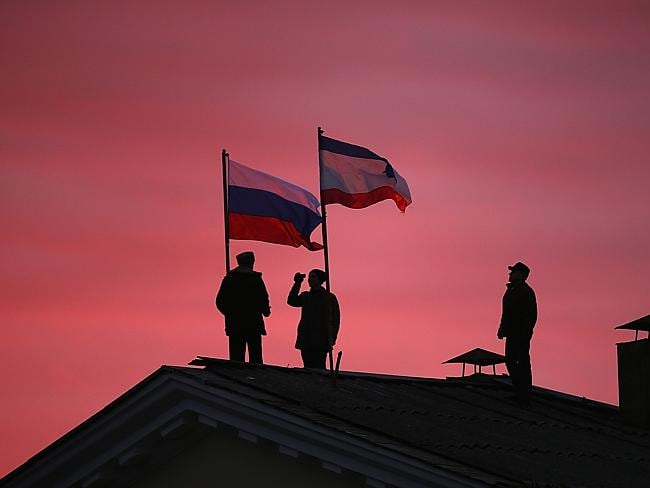 Russia and Crimea rejoined ... Cossack men install a Russian flag and a Crimean flag on the roof of the City Hall in Bakhchysarai, Ukraine. Picture: Dan Kitwood