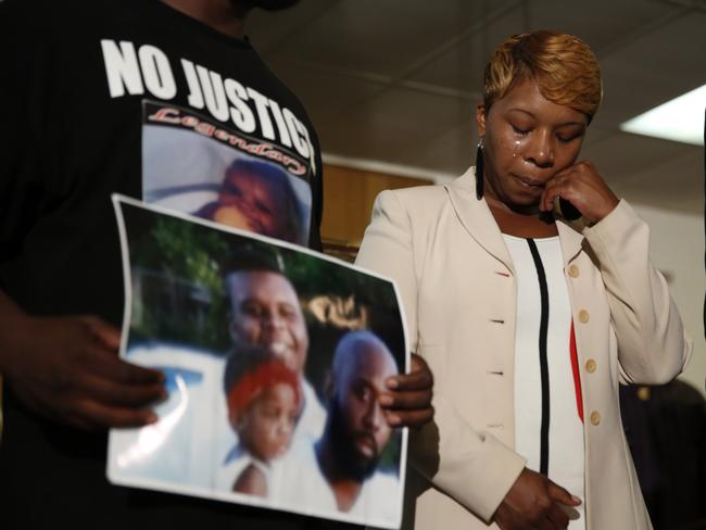 Lesley McSpadden, the mother of 18-year-old Michael Brown, wipes away tears as Brown's father, Michael Brown Sr., holds up a family picture of himself, his son, top left, and a young child. AP Photo/Jeff Roberson