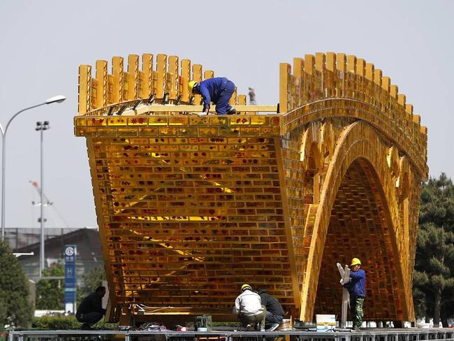 Workers install the 'Golden Bridge of Silk Road' outside a summit showcasing President Xi Jinping's signature foreign-policy plan 'One Belt, One Road'. Picture: AP