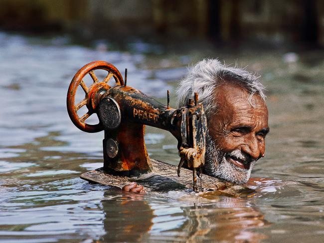 Steve McCurry: India exhibtion - Tailor carries his sewing machine through monsoon waters, Porbandar, Gujarat Steve McCurry, 1983. Picture: Steve McCurry