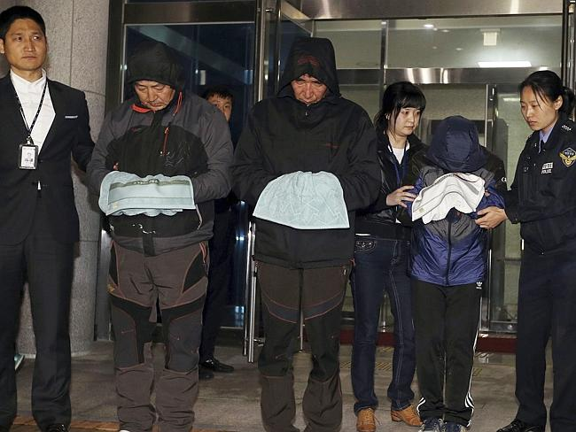 In custody ... Lee Joon-seok, third from left, the captain of the ferry Sewol that sank off South Korea, and two crew members prepare to leave a court which issued their arrest warrant in Mokpo. Picture: AP/Yonhap