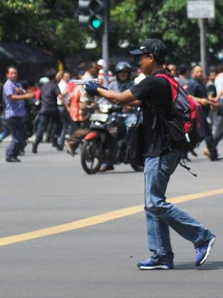 Threatening bystanders ... an attacker with a gun ready to open fire. Picture: AP