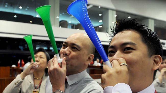 Filipino traders blow horns to mark the first trading day of the year after Philippine share prices closed 0.83 percent higher, up 48.26 points to close at 5,860.99, to a new all-time high on rising optimism that the US fiscal cliff would be averted, dealers said. Picture: AFP/ JAY DIRECTO