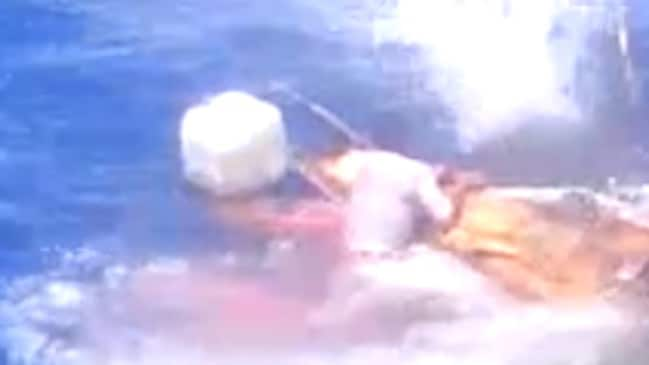 Horrific ... one of the men appears to cling to the boat while shots are fired at him.