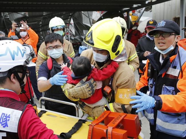 Discovered ... a baby boy is rescued from a collapsed building after an earthquake in Tainan, Taiwan. Picture: AP Photo/Wally Santana